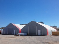 Industrial warehouse fabric structure with roll-up door.